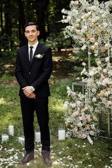 Der bräutigam steht in der nähe des altars. hochzeitszeremonie, bei der der glückliche bräutigam auf die braut wartet. hochzeitstag. bräutigam im schwarzen anzug bei der ausgangszeremonie