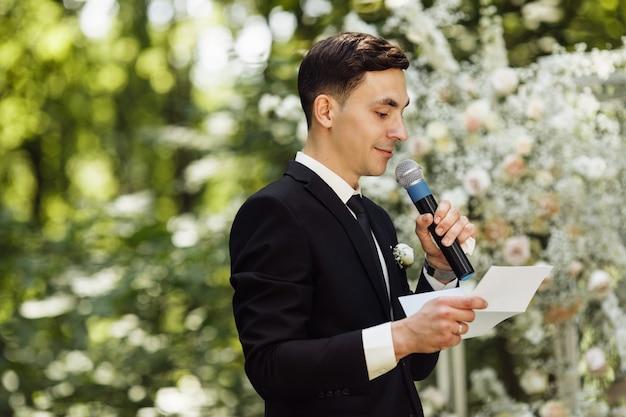 Der bräutigam steht in der nähe des altars. hochzeitszeremonie, bei der der glückliche bräutigam auf die braut wartet. hochzeitstag. bräutigam im schwarzen anzug bei der ausgangszeremonie Premium Fotos