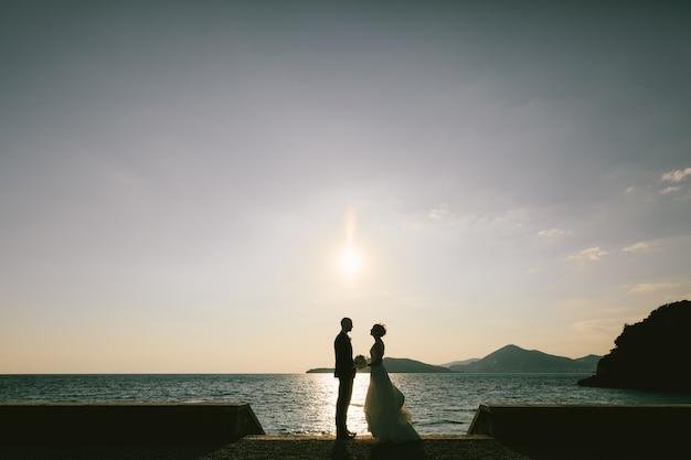 Der bräutigam steht vor der braut in einem weißen kleid mit einem blumenstrauß auf der böschung bei der