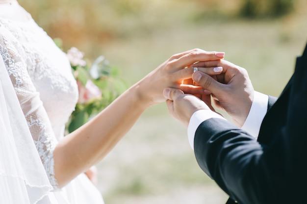 Der bräutigam trägt die braut einen ehering bei der zeremonie.