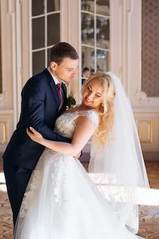 Der bräutigam umarmt die braut an der taille und möchte küssen