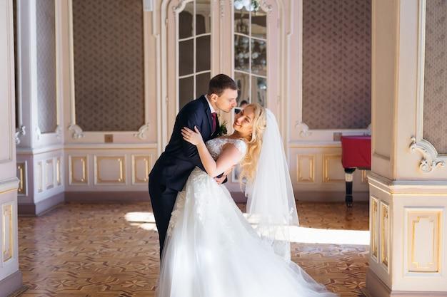 Der bräutigam umarmt die braut an der taille und sie beugt sich zurück und lächelt schöne halle