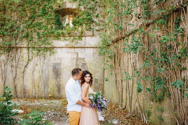 Der bräutigam umarmt die braut in einem schönen pastellkleid mit blumenstrauß gegen die szene eines