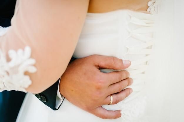 Der bräutigam umarmt die braut mit den händen hinter der taille und steht auf der hochzeitszeremonie im freien im naturhinterhof.