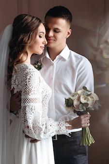 Der bräutigam umarmt die braut sanft in einem wunderschönen boho-hochzeitskleid. hochzeitsfoto-session des brautpaares.