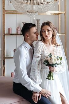 Der bräutigam umarmt die braut sanft in einem wunderschönen spitzenkleid mit einem strauß frischer blumen. hochzeitsfoto-session