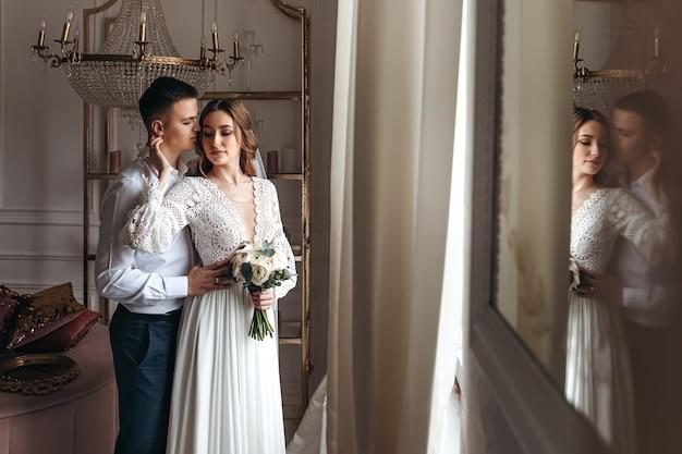 Der bräutigam umarmt die braut sanft in einem wunderschönen spitzenkleid mit einem strauß frischer blumen.
