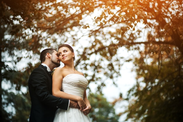 Der bräutigam umarmt die braut sanft mit einem blumenstrauß von hinten in einem park