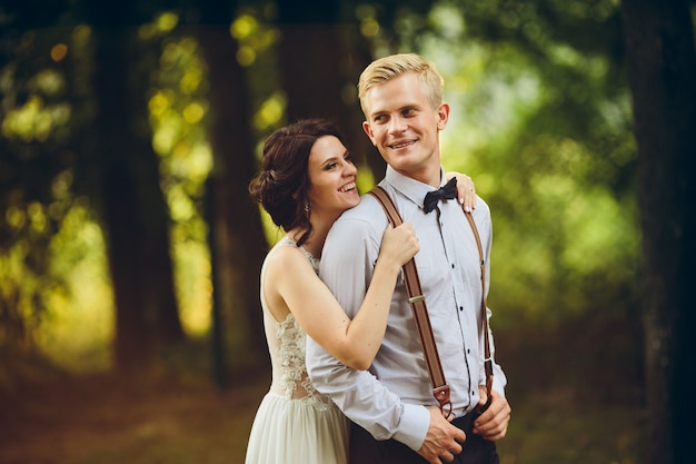 Der bräutigam umarmt ihren bräutigam sanft im wald