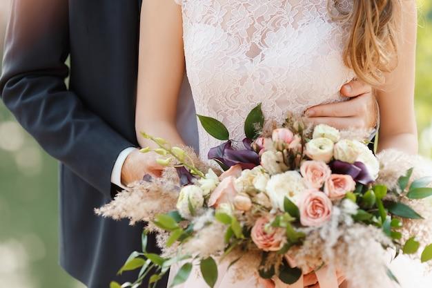 Der bräutigam umarmt sanft die braut hinter sich