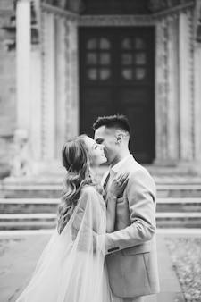 Der bräutigam umarmt und küsst die braut am eingang zur basilika von santa maria