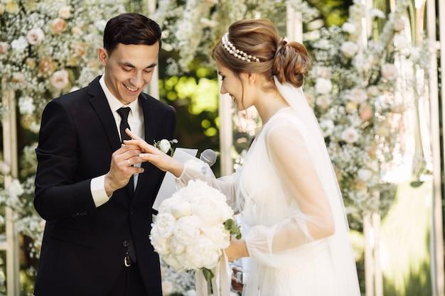 Der bräutigam und die braut lasen sich während der hochzeitszeremonie versprechen. jungvermählten tauschen ringe aus. bräutigam mit der braut am hochzeitsbogen.