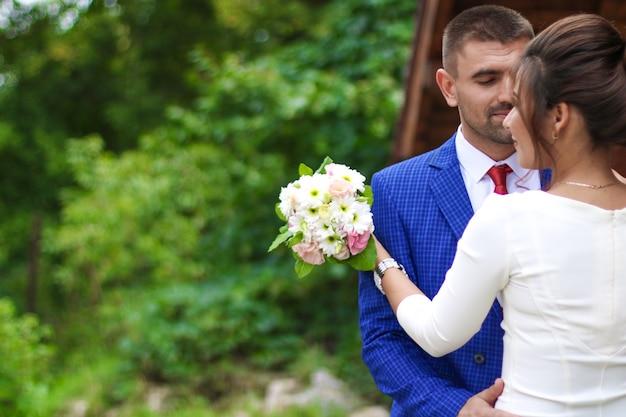 Der bräutigam und die braut mit dem brautstrauß in der hand vor dem hintergrund der natur
