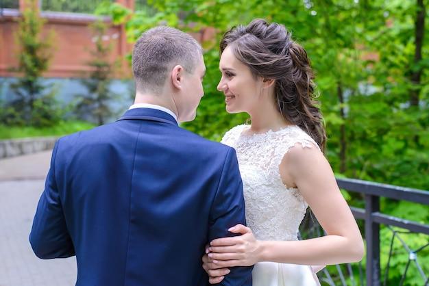 Der bräutigam und die braut stehen schön und schauen sich mit liebe im sommerpark an
