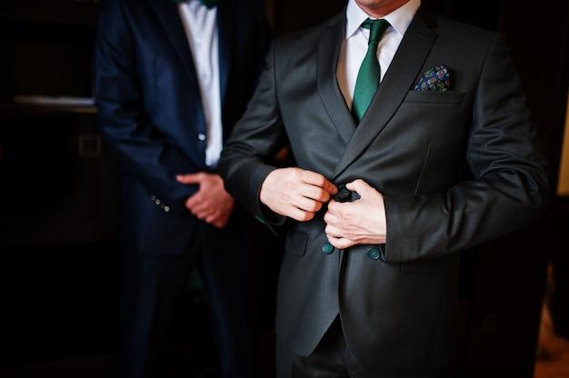 Der bräutigam verkleidet sich in gegenwart seiner trauzeugen im zimmer.