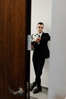 Der bräutigam wartet auf die braut, die unter der tür steht und einen hochzeitsstrauß aus rosen hält