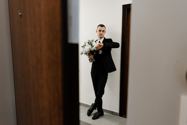 Der bräutigam wartet auf die braut, die unter der tür steht und einen hochzeitsstrauß aus rosen in der hand hält.