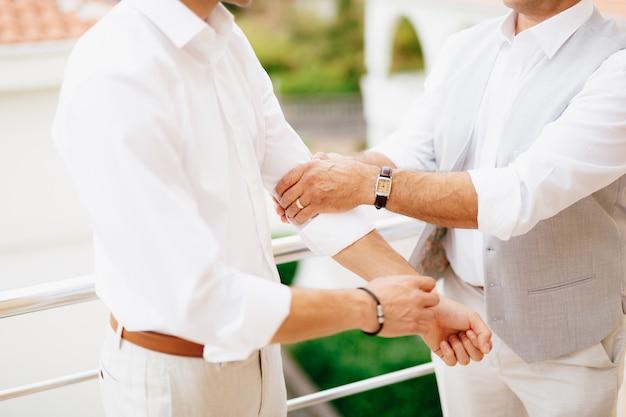 Der bräutigam zieht die ärmel seines hemdes hoch, während er sich auf die hochzeitszeremonie vorbereitet