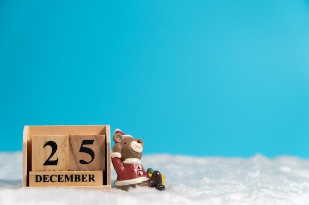 Der braunbär, der einen weihnachtshut sitzt auf hölzernem kalender trägt, stellte am weihnachtsdatum 25 ein