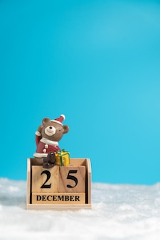Der braunbär, der einen weihnachtshut sitzt auf holzblockkalender trägt, stellte auf weihnachten d ein