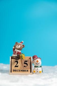 Der braunbär, der einen weihnachtshut tragen und ein schneemann, der auf dem holzblockkalender sitzt, stellte auf ein