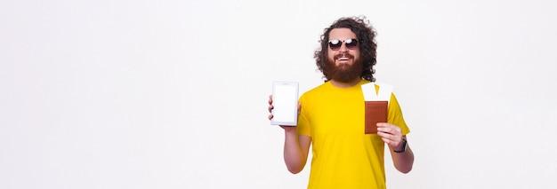 Der breite lächelnde mann zeigt den pass und den bildschirm des tablets, das er hält.