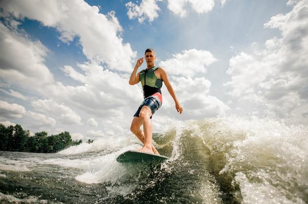 Der brünette kaukasische surfer übt seine beruflichen fähigkeiten aus