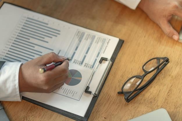 Der buchhalter prüft dokumente zu grafiken und diagrammen, die sich auf die rechnungslegung und die steuerbilanzierung des unternehmens beziehen