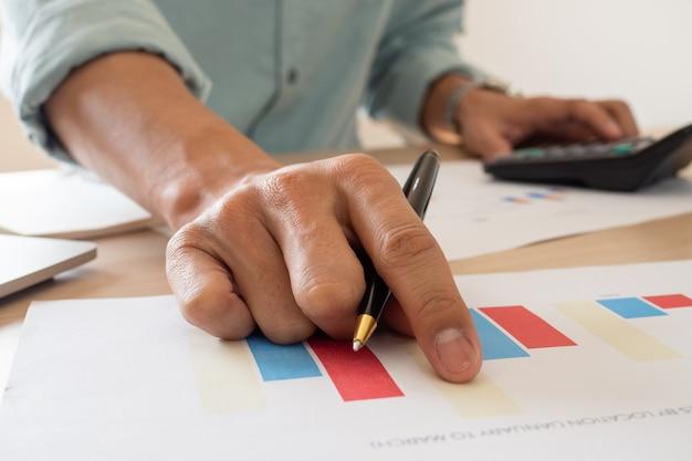 Der buchhalter überprüft die ausgaben- und investitionsberichte des unternehmens anhand der grafischen dokumente