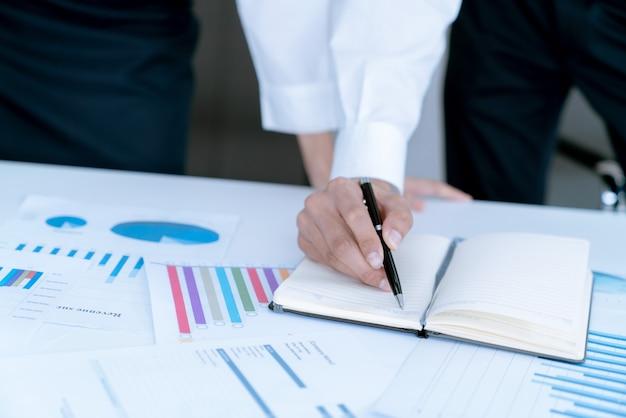 Der buchhalter überprüft dokumente über graph- und diagrammberichterstattung und steuern