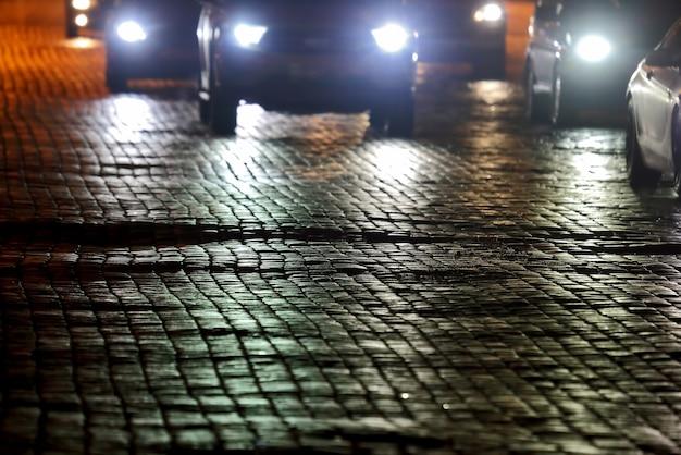 Der bürgersteig der straße bei nacht im licht der autos