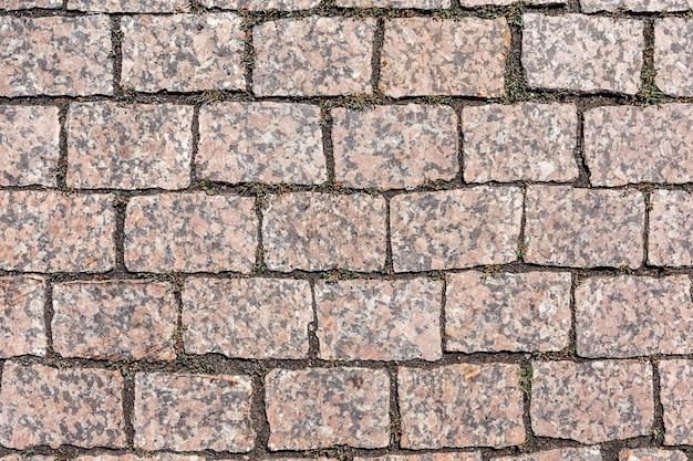 Der bürgersteig ist mit roten granitpflastersteinen gepflastert natürlicher hintergrund und textur des steins