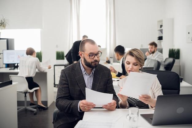 Der business coach unterrichtet die auszubildenden in einem geräumigen büro. ausbildung von neuankömmlingen, praktika in einem großen unternehmen.