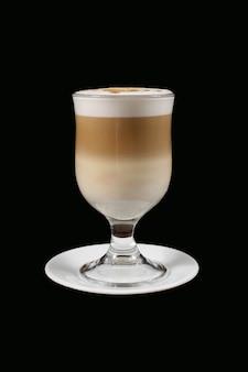 Der cappuccino aus transparentem glas auf schwarz