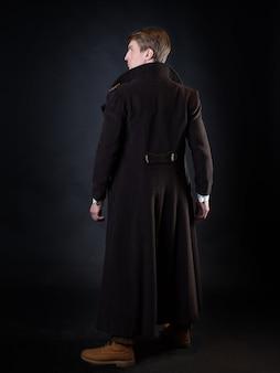 Der charakter der steampunk-geschichte, ein junger attraktiver mann in einem eleganten langen mantel. intelligenter gentleman im viktorianischen stil. vintage retro-anzug, junger attraktiver mann in weste und fliege