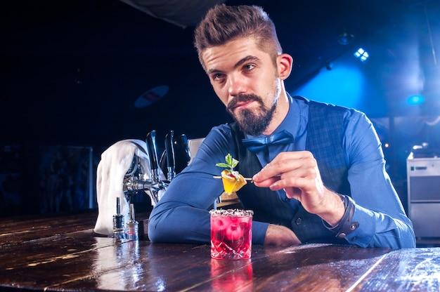 Der charmante barkeeper mischt einen cocktail, während er in der bar neben der theke steht