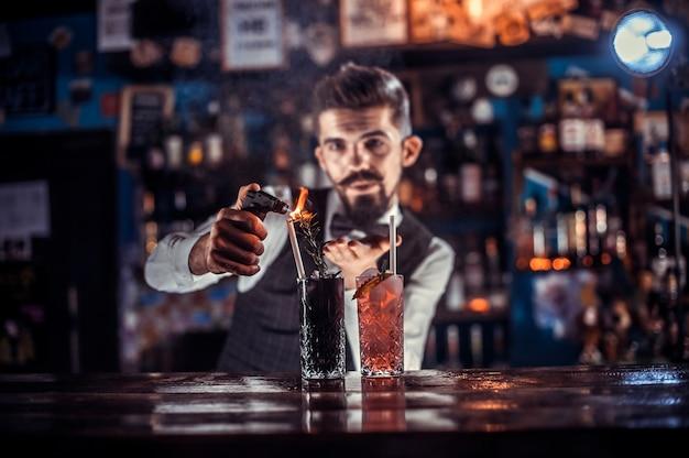 Der charmante barmann gießt an der theke einen drink ein