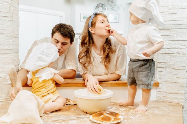 Der charmante zweijährige junge versucht mit seiner mutter, pfannkuchen zu backen, während er mit papa und schwester in der familie kocht. konzept von hobbys und gemeinsamen entwicklungserfahrungen mit kindern