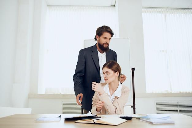 Der chef belästigt die sekretärin bei der arbeit im büro von gewalt belästigt. foto in hoher qualität