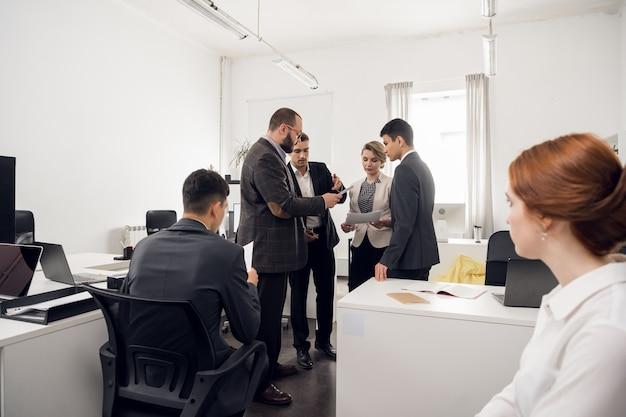 Der chef der baufirma hält ein ständiges treffen mit untergebenen ab, gibt anweisungen und fordert einen bericht über die im büro geleistete arbeit.