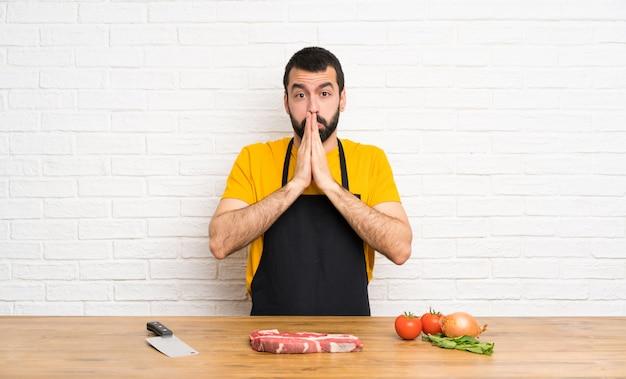 Der chef, der in einer küche hält, hält palme zusammen. person bittet um etwas