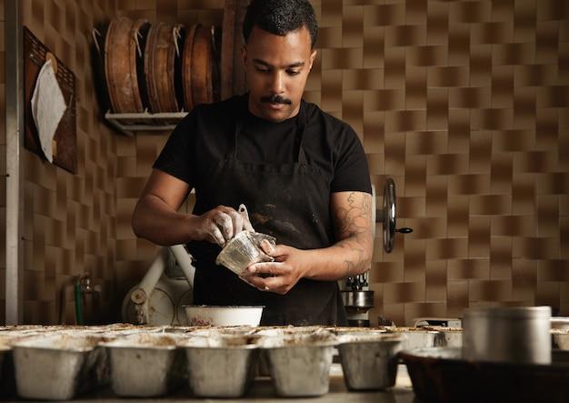 Der chef des schwarzen mannes bereitet kuchenformen vor, bevor er sie in seiner professionellen konditorei mit teig füllt