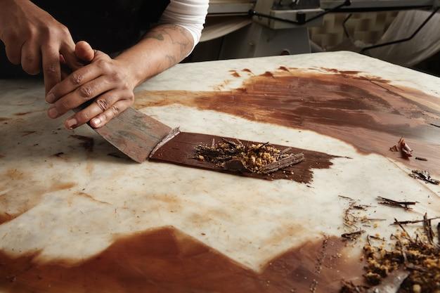 Der chef des schwarzen mannes sammelt gekühlte geschmolzene schokolade vom marmortisch, nahes abstraktes bild der arbeit in der schokoladenkonfektion