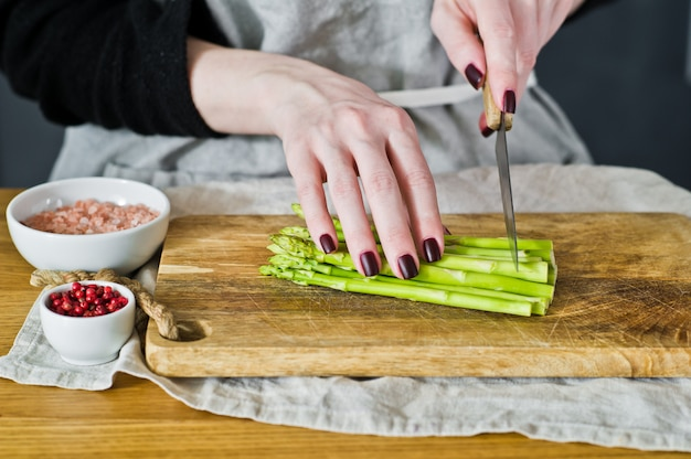 Der chef schnitt minispargel seitenansicht, küche, konzept des kochens des spargels im speck
