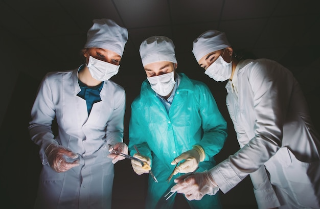 Der chirurg führt eine operation in einem dunklen raum durch.