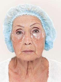 Der chirurg führt vor der plastischen operation eine hautuntersuchung bei einer frau mittleren alters durch
