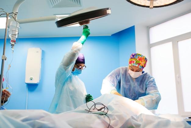 Der chirurg stellt die lampe im operationssaal ein