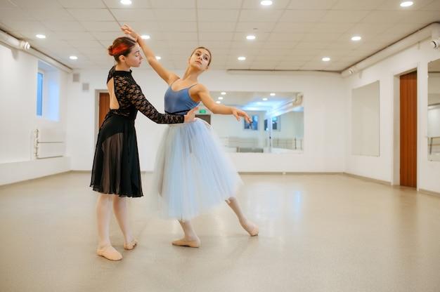 Der choreograf arbeitet mit jungen ballerina im unterricht. ballettschule, tänzerinnen im choreografieunterricht, mädchen, die gnadentanz üben