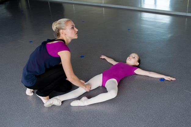 Der choreograf bringt dem kind die richtige haltung bei.