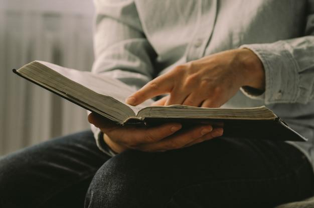 Der christ hält die bibel in seinen händen. die bibel lesen. das konzept von glauben, spiritualität und religion